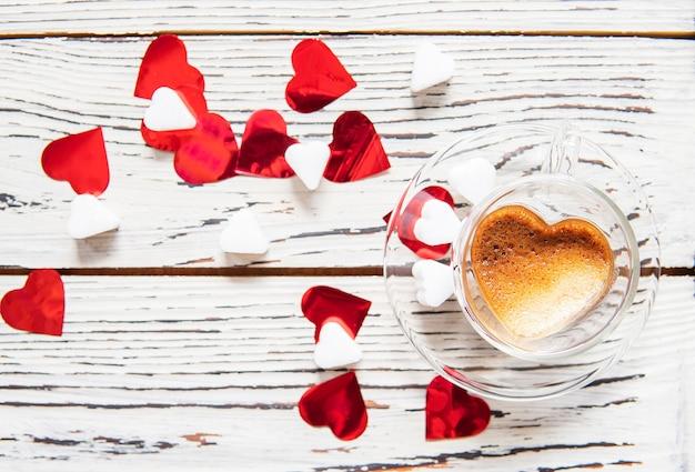 Kaffeetasseherz formte mit konfettis und zucker auf weißem holz.