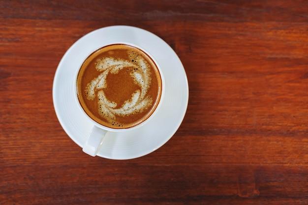 Kaffeetassen auf einem holztisch in einem kaffeehaushintergrund