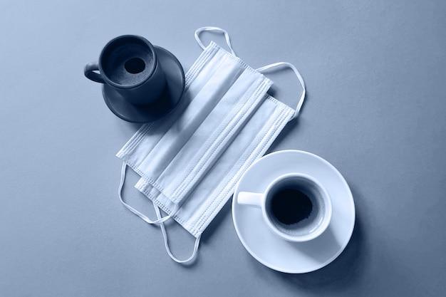 Kaffeetassen und entfernte medizinische masken. frühstück im cafe. draufsicht, flache lage, schwarzweißfoto.
