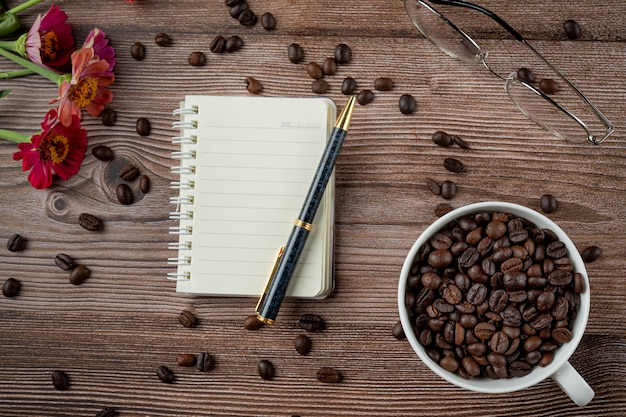 Kaffeetassen und kaffeebohnen auf dem tisch, internationaler tag des kaffeekonzepts.