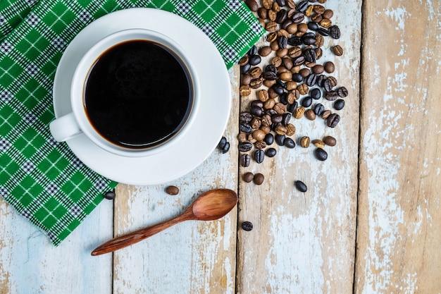 Kaffeetassen und kaffeebohnen auf dem tisch