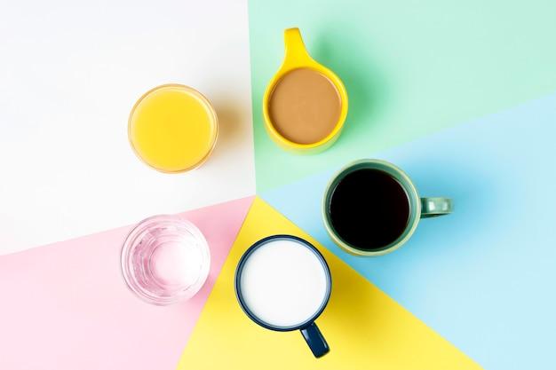 Kaffeetee und andere getränke in den bunten schalen auf einem mehrfarbigen hintergrund, draufsicht