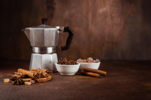 Kaffeetopf mit gewürzen auf braunem hintergrund.