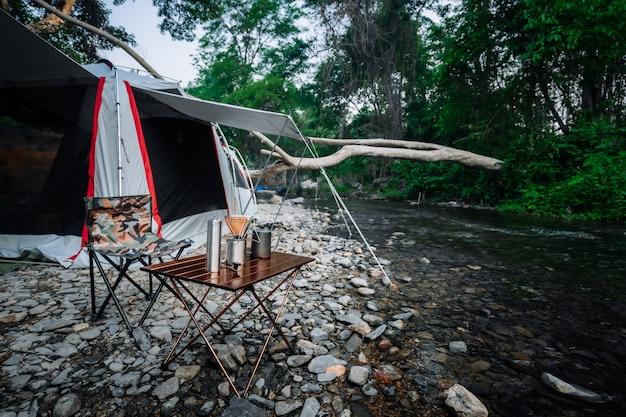 Kaffeetropfen beim zelten in der nähe des flusses im naturpark