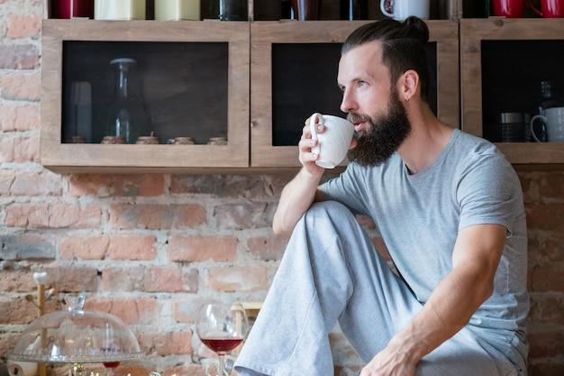 Kaffeezeit. morgenbetrachtung. absicht. junger bärtiger hipster mit weißer tasse, die auf küchentheke sitzt.