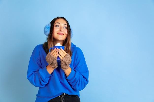 Kaffeezeit. porträt der kaukasischen frau auf blauem studiohintergrund. schönes weibliches modell in warmer kleidung. konzept der emotionen, gesichtsausdruck, verkauf, anzeige. winterstimmung, weihnachtszeit, feiertage.