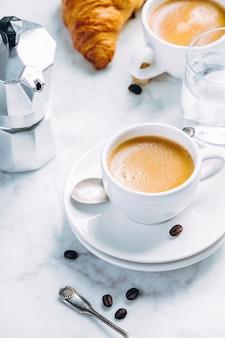 Kaffeezusammensetzung auf weißem marmor. kaffee espresso in weißen tassen