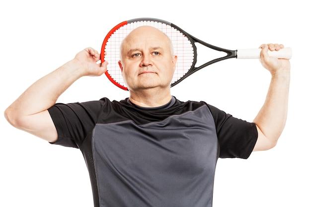 Kahler gealterter mann in einem schwarzen sporthemd mit einem tennisschläger. isoliert.