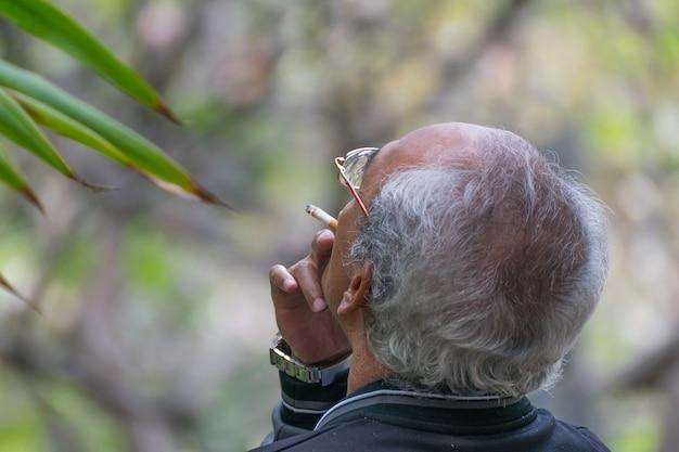 Kahler kopf und weißes haar asien-erwachsener, der im park raucht