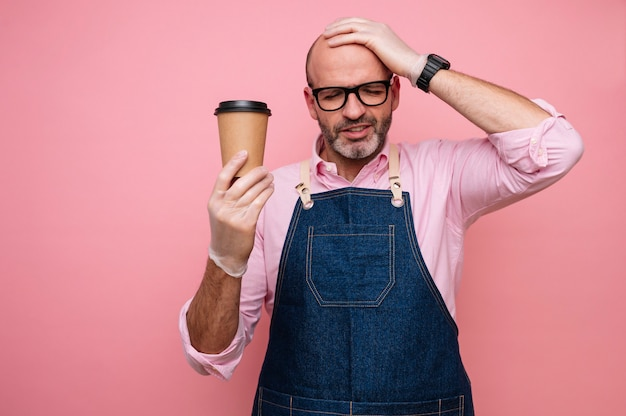 Kahler reifer mann mit hand auf kopf und kaffee im recycelbaren pappbecher