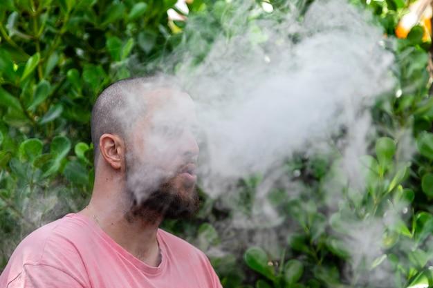 Kahlköpfiger und bärtiger mann, der raucht.