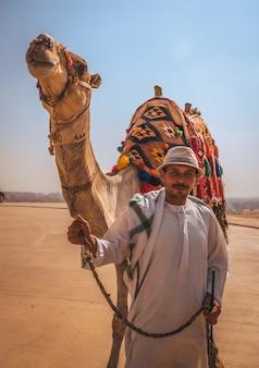 Kairo, ägypten; oktober 2020: porträt eines lokalen verkäufers mit seinem kamel in der kefren-pyramide. die pyramiden von gizeh sind das älteste grabdenkmal der welt