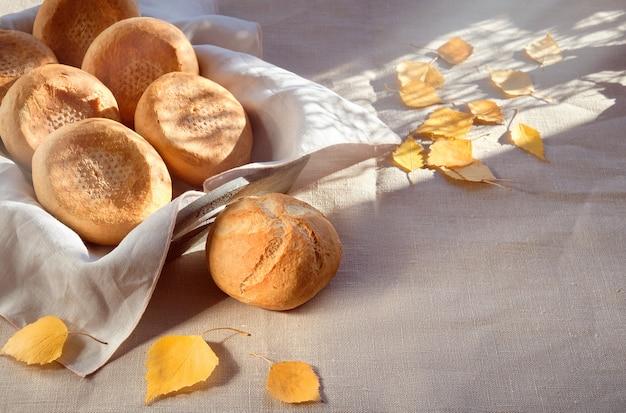 Kaiser- oder wiener brötchen im brotkorb auf textiler tischdecke mit gelbem herbstlaub.