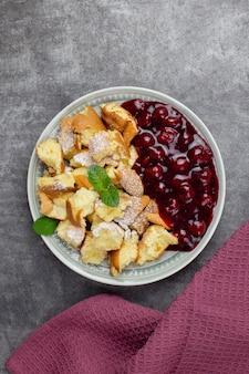 Kaiserschmarren oder kaiserschmarrn ist ein traditionelles österreichisches oder deutsches süßes pfannkuchendessert mit puderzucker und beeren, kirschsauce oder roter grutze-marmelade.