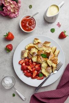 Kaiserschmarren oder kaiserschmarrn, traditionelles österreichisches oder deutsches süßes pfannkuchendessert, mit beeren-, erdbeermarmelade oder rote grutze und vanillepudding-sauce.