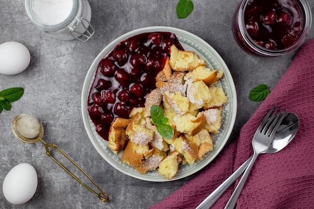 Kaiserschmarrn ist ein traditionelles österreichisches oder deutsches süßes pfannkuchendessert mit kirschsauce oder marmelade.