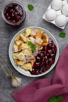 Kaiserschmarrn ist ein traditionelles österreichisches oder deutsches süßes pfannkuchendessert mit puderzucker und beeren, kirschsauce oder roter grutze-marmelade.