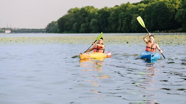 Kajak mit zwei männern paddelt auf ruhigem see
