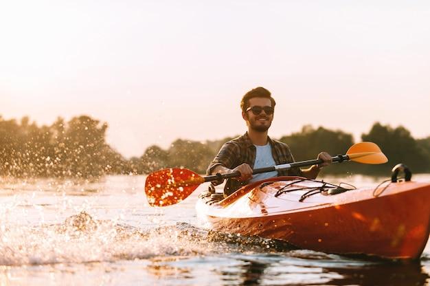 Kajakfahren auf dem fluss. hübscher junger lächelnder mann, der beim kajakfahren auf dem fluss wasser spritzt