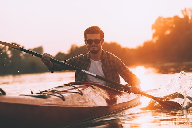 Kajakfahren ist mein leben! junger lächelnder mann, der auf dem fluss mit sonnenuntergang im hintergrund kajak fährt