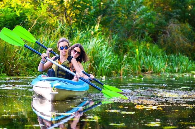 Kajakfahren mit der familie, mutter und tochter, die im kajak auf der flusskanutour spaß haben paddeln