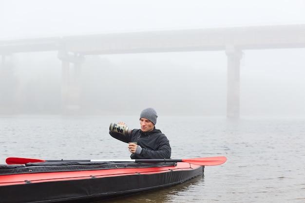Kajakfahrer, der einen snack auf seinem boot hat, mitten im fluss posiert und heißen tee aus der thermoskanne trinkt
