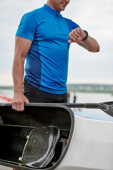 Kajakfahrer hält boot und schaut auf seine uhr auf einem pier