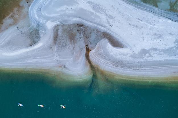 Kajaktouristen auf dem meer und weißen strand draufsicht