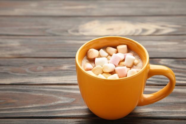 Kakao im gelben becher mit marshmallows auf braunem hintergrund