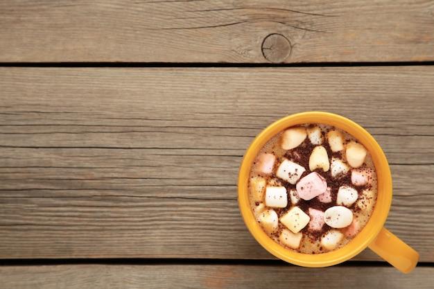 Kakao im gelben becher mit marshmallows auf grauem hintergrund