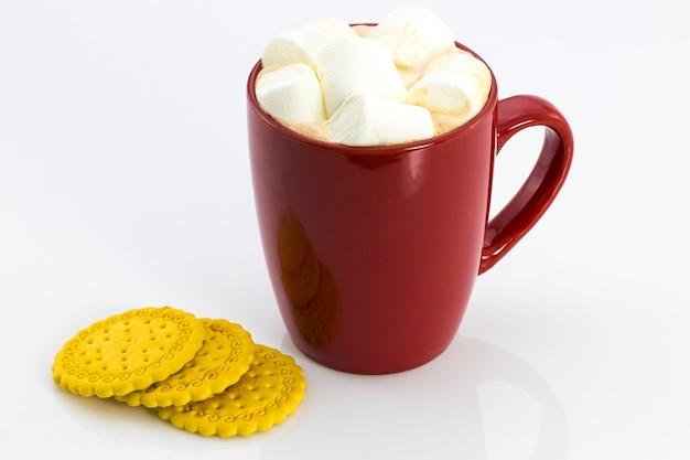 Kakao im roten becher mit marshmallows und keksen, lokalisiert auf weißem hintergrund