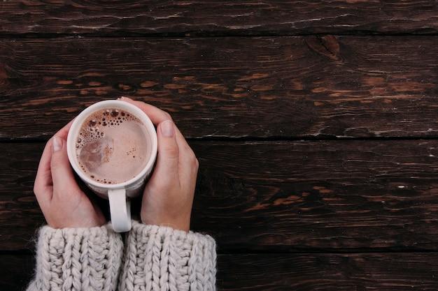 Kakao in den händen auf einem hölzernen hintergrund