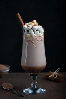 Kakao in hohem glas mit weißem marshmallow und zimtstange auf dunkelbraunem holztisch