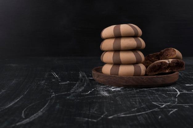 Kakao-keks-brötchen in einem stapel in einer holzplatte