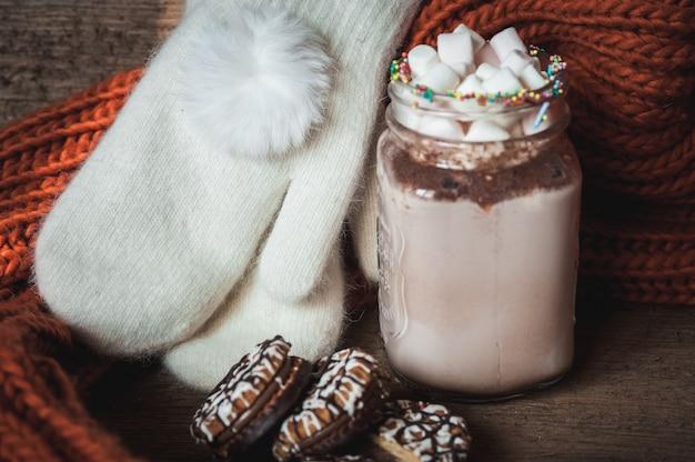 Kakao mit marshmallows, schokoladenkeksen, gestricktem orangenschal und weißen fäustlingen