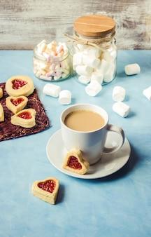 Kakao mit marshmallows und einem plätzchenherzen. selektiver fokus