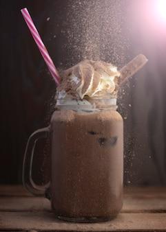 Kakao-smoothie mit sahne, mit fallenden spänen, an dunkler wand