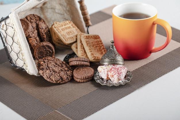 Kakao- und butterkekse in einem korb mit einer tasse tee