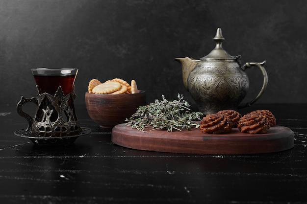 Kakao und butterplätzchen auf einem holzbrett mit tee.