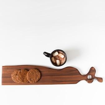 Kakaobecher nahe dekorativem schneidebrett mit plätzchen