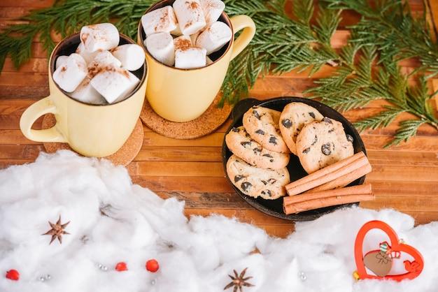 Kakaobecher und plätzchenplatte nahe weihnachtsdekorationen