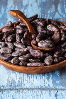 Kakaobohnen in der hölzernen schüssel auf blauem rustikalem
