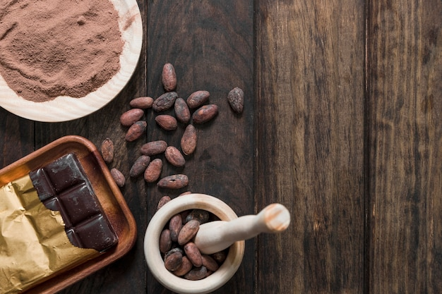 Kakaobohnen mit kakaopulver und eingewickeltem schokoriegel auf holztisch