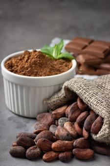 Kakaobohnen, pulver und schokolade auf grauem steinhintergrund.