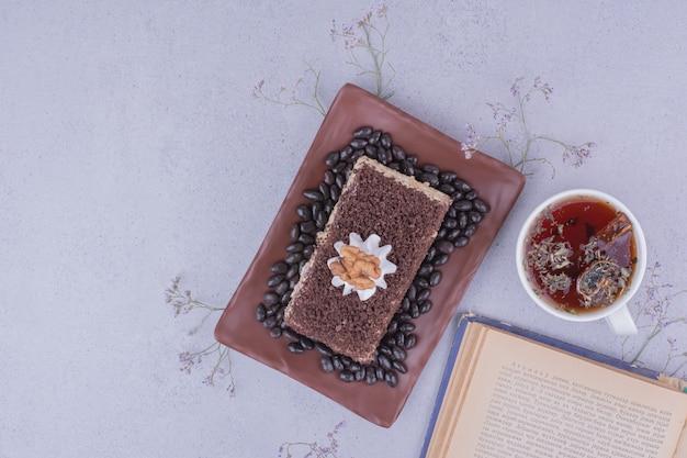 Kakaokuchenscheibe mit walnuss und einer tasse kräutertee.