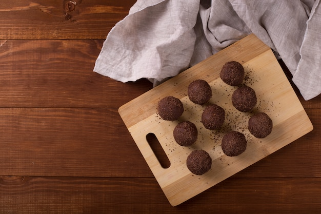 Kakaokugeln, schokoladentrüffelkuchen an bord auf holztisch