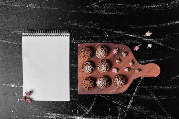 Kakaoplätzchen auf einem holzbrett mit einem rezeptbuch beiseite.