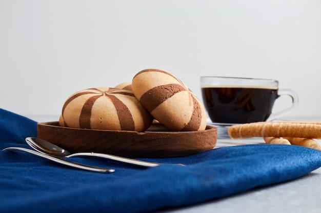 Kakaoplätzchen mit einer tasse kaffee auf blauer tischdecke.