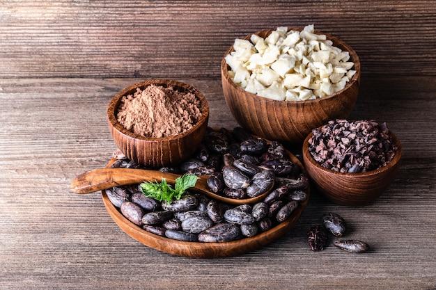 Kakaoprodukte im hölzernen schüssellöffel auf alter rustikaler tabelle.