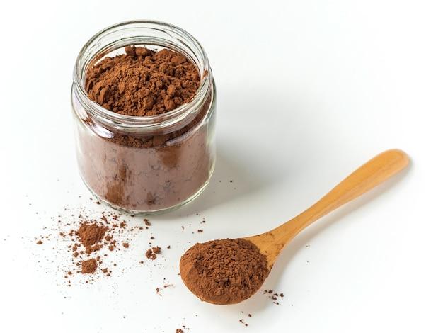 Kakaopulver auf einem löffel und einem glas